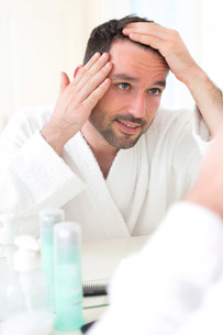 Young attractive man taking care of his hairの素材 [FYI00792550]