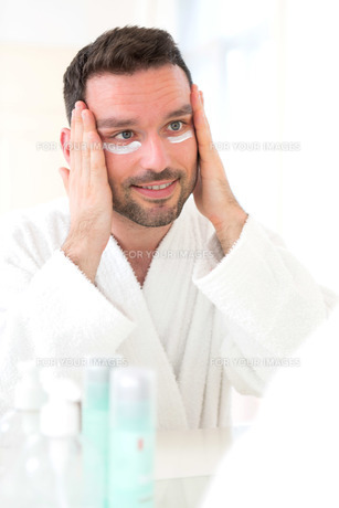 Young attractive man applying anti dark circles cream around eyesの素材 [FYI00792556]