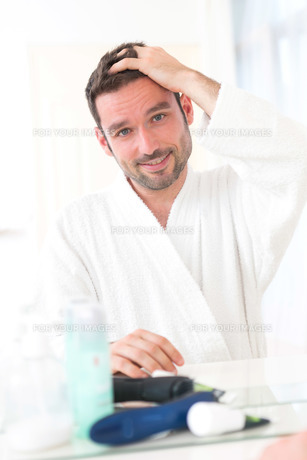Young attractive man taking care of his hairの素材 [FYI00792557]