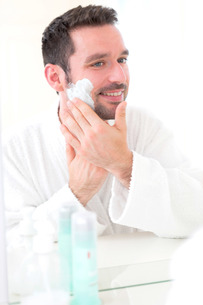 Young attractive man shaving his beard in front of a mirrorの素材 [FYI00792565]