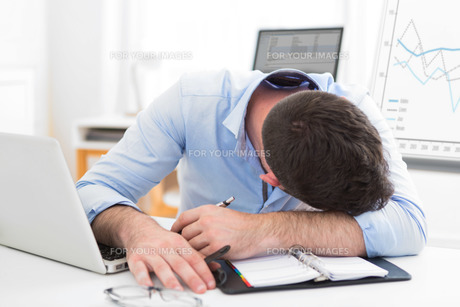 Young attractive man too tired to workの写真素材 [FYI00792567]