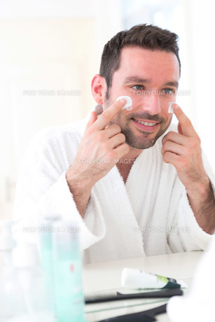 Young attractive man applying anti dark circles cream around eyesの素材 [FYI00792569]