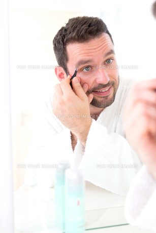 Young attractive man tweezing his eyebrowの素材 [FYI00792579]