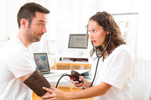 Young attractive doctor checking patient's blood pressureの写真素材 [FYI00792592]