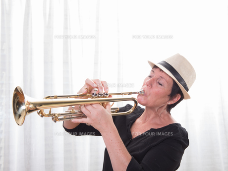 attractive woman with hat playing the trumpetの写真素材 [FYI00793080]