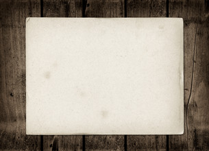 Old textured paper sheet on a dark wood tableの写真素材 [FYI00793436]