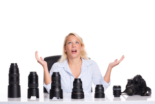 woman sitting in front of different lenses and can not decideの写真素材 [FYI00794217]