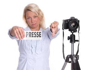 blonde press photographer showing thumbs downの写真素材 [FYI00794220]