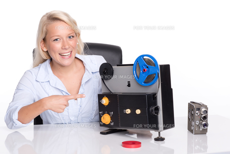 blonde woman pointing at an old movie projectorの写真素材 [FYI00794221]