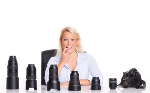 photographer sitting in front of different lenses and consideredの写真素材 [FYI00794237]