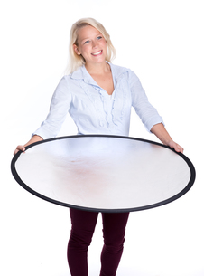 blond woman holding a photograph reflectorの写真素材 [FYI00794243]