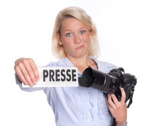press photographer with camera contorts her faceの写真素材 [FYI00794247]