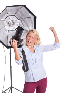 woman with camera in photo studio showing enthusiasmの写真素材 [FYI00794268]