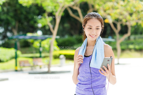 Sporty girl listen to music after runningの写真素材 [FYI00794493]