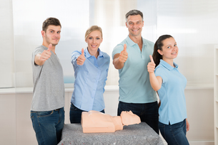 People With Thumbs Up Sign While Learning Resuscitationの写真素材 [FYI00794628]