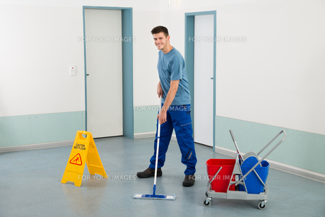 Male Worker With Cleaning Equipments Mopping Floorの写真素材 [FYI00794664]