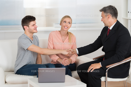 Consultant Shaking Hands To Coupleの写真素材 [FYI00794667]