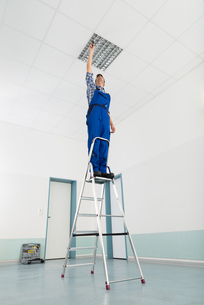 Electrician Installing Ceiling Lightの写真素材 [FYI00794668]