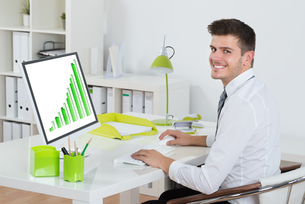Young Businessman Analyzing Graph On Computerの写真素材 [FYI00794683]