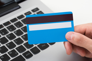 Person Hands With Credit Card Over Laptop Keypadの写真素材 [FYI00794687]