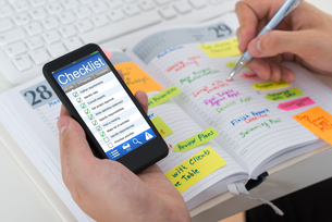 Person Checking List From Mobile Phone And Diaryの写真素材 [FYI00794733]