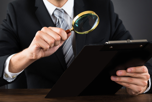 Businessperson Inspecting Document With Magnifying Glassの写真素材 [FYI00794737]