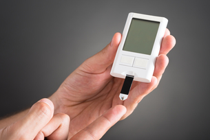 Person Checking Blood Sugar Level With Glucometerの写真素材 [FYI00794801]