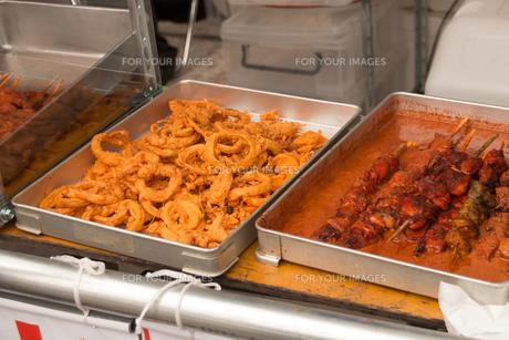 フェスティバルの屋台の食べ物。インド料理、オニオンリングフライ、シシカバブ、タンドリーチキン、串焼きの写真素材 [FYI00796263]