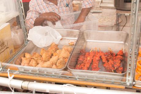 インド料理、サモサとシシカバブを販売する外国の女性店員。フェスティバルの屋台の食べ物。の写真素材 [FYI00796265]