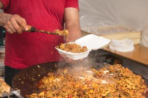 フェスティバルの屋台の食べ物。インドカレーを販売する男性店員の写真素材 [FYI00796266]
