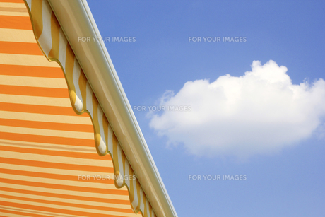 sun awning in front of blue sky yellow whiteの写真素材 [FYI00810266]
