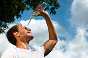 sportsman throwing water over his head for refreshmentの写真素材 [FYI00811457]