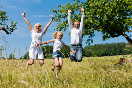 happy family outdoors jumping highの写真素材 [FYI00812944]