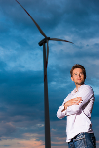 man in front of a wind turbine and skyの写真素材 [FYI00812969]