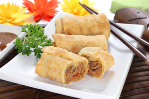 spring rolls with ground beef,tomatoes,parsley and garlic on a white backgroundの写真素材 [FYI00813542]