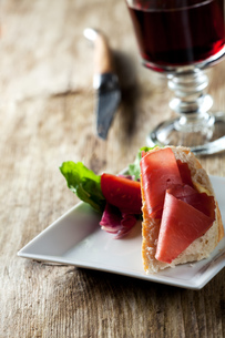 close up of a ham sandwich and red wineの写真素材 [FYI00814175]