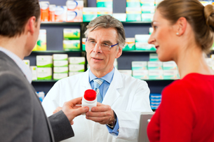 pharmacist in his pharmacy with customersの写真素材 [FYI00815649]