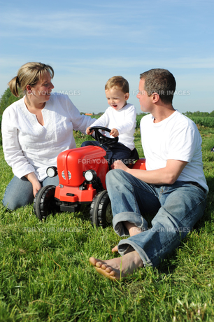 parents and child with red toy tractorの写真素材 [FYI00816281]