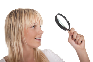 young blonde woman with magnifying glassの写真素材 [FYI00816666]
