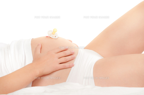 pacifier on belly of a beautiful pregnant womanの写真素材 [FYI00819848]