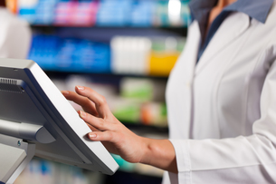 pharmacist standing at the cashier in pharmacyの写真素材 [FYI00820304]