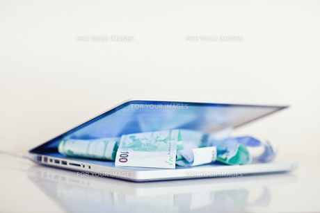 laptop with banknotesの写真素材 [FYI00820679]