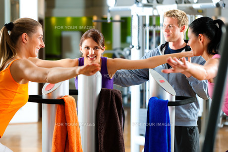 women and trainer in gym before training machineの写真素材 [FYI00820859]