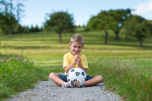 boy with soccer ball sits on a dirt roadの写真素材 [FYI00825881]