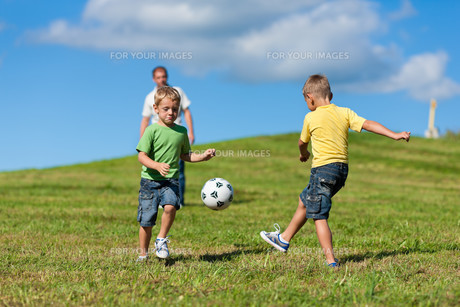 happy family is playing soccer in summerの写真素材 [FYI00825888]
