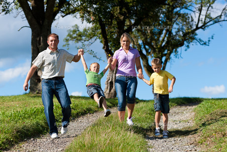 family outdoors is running on a dirt roadの写真素材 [FYI00825910]