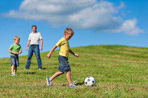 happy family is playing soccer in summerの写真素材 [FYI00825945]