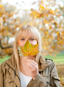 young woman with autumn leafの写真素材 [FYI00831584]