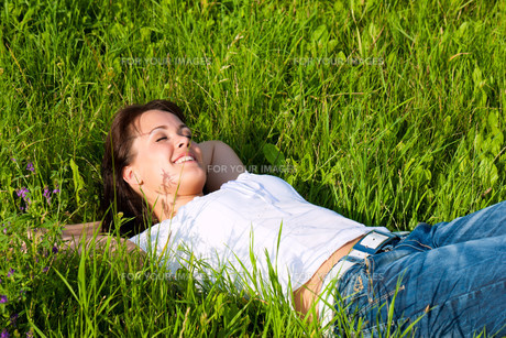 woman lying on a lawn and is dreamingの写真素材 [FYI00834977]