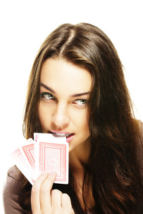 young woman chooses poker card with her teethの写真素材 [FYI00836869]